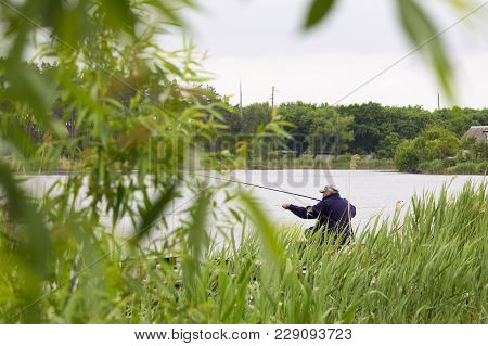 The Fisherman Is Fishing On The River With A Fishing Rod
