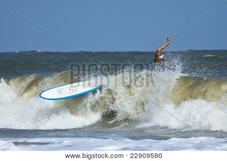 man wiping out on surfboard in heavy atlantic surf.