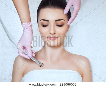 poster of The cosmetologist makes the procedure Microdermabrasion of the décolletage skin of a beautiful, young woman in a beauty salon.Cosmetology and professional skin care.