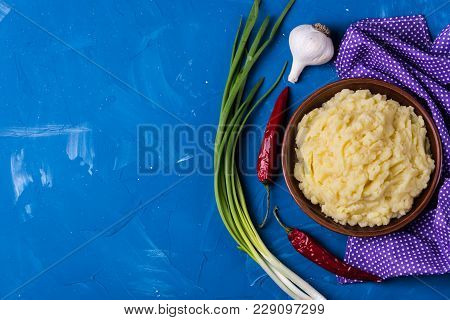 Mashed Potatoes Bowl With Pepper,onion And Garlic On Blue Background