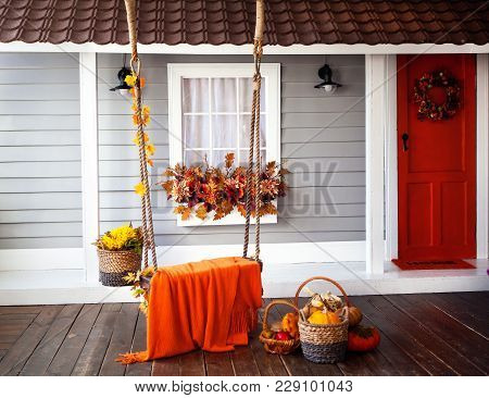 Interior Of An Autumn Patio. Swing Is Adorned With Autumn Leaves And Orange Knitted Plaid. Basket Wi