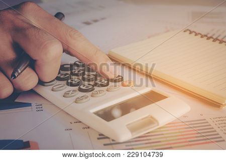 Business Concept, Close Up Man Hand Using Calculator And Writing Make Note With Calculate At Office.