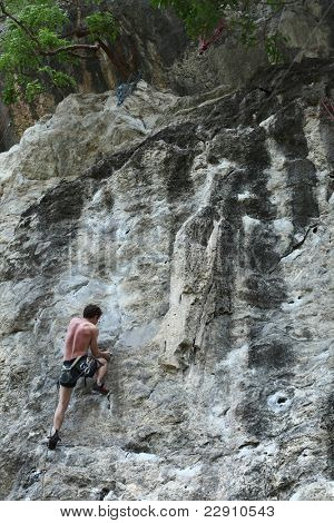 Young semi naked man climbing on a rock with belay