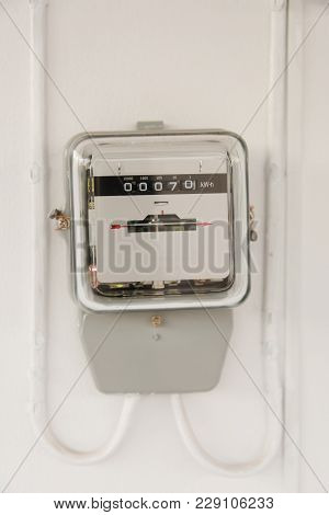 Analog Electric Meter On Cement Wall. Electricity Consumption Concept.