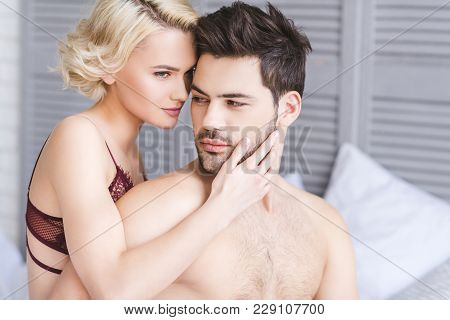 Seductive Young Couple Of Lovers Embracing On Bed