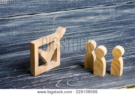 Three Wooden Human Figures Stand Together Next To A Tick In The Box. The Concept Of Elections And So