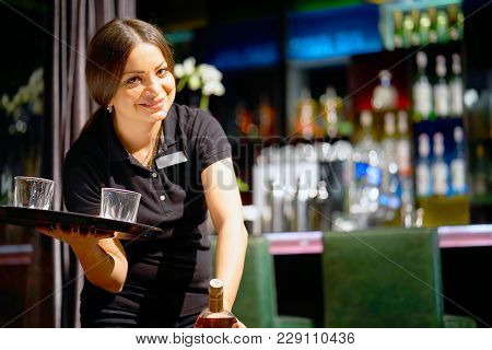 A Barmaid Girl Carries A Bottle Of Whiskey On A Tray To The Client Of The Hotel Bar. The Concept Of