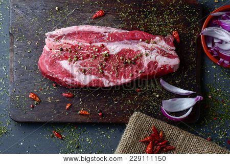 high angle view of a raw strip steak seasoned with different spices, such pepper corns of different colors, chili peppers or oregano, on a dark wooden chopping board placed on a gray wooden a table