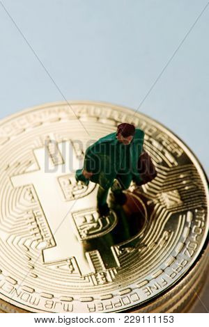 closeup of a miniature man carrying a suitcase on a pile of bitcoins against an off-white background with some blank space on top