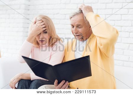 A Man In A Yellow Cardigan And A Woman In A Pink Sweater Are Sitting And Reading Documents In A Blac