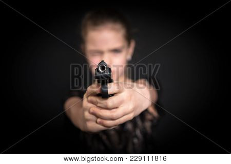 Girl Aiming A Gun At The Camera, Blurred Background, On Black