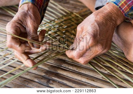 Old Man Hands Manually Weaving Bamboo. In A Traditional Village