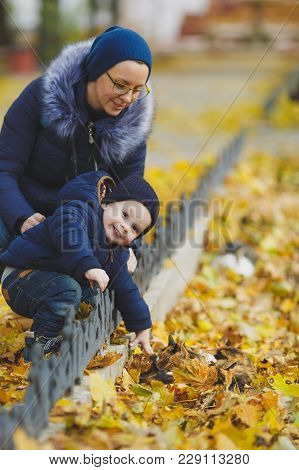 Woman Walking In Yellow Fall Park With Little Cute Child Baby Boy On Nature. Mother, Small Kid Son S