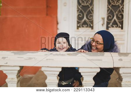 Young Woman With Little Cute Child Baby Boy Look Out From Behind The Handrail Railing With Columns.