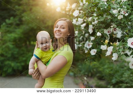 Young Tender Woman Standing Near Green Bush, White Flowers Background, Hugging Little Cute Child Bab