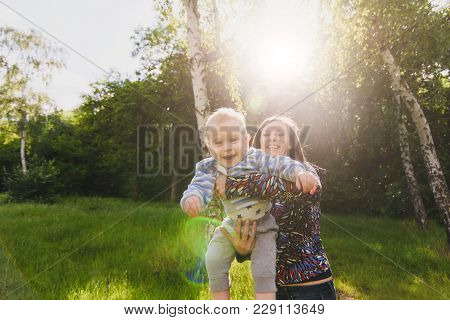 Young Joyful Woman Walking On Nature Park Background Holding On Hands, Circling Little Cute Child Ba