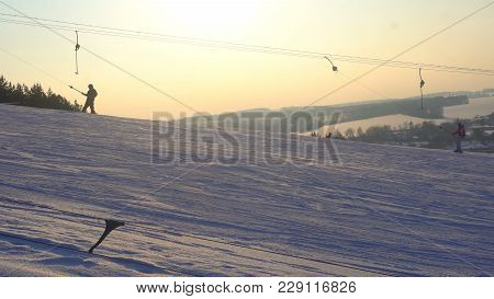 Landscape Winter Slides Ski Resort, Ski Lift, Going Down Downhill Snowboarders And Skiers.