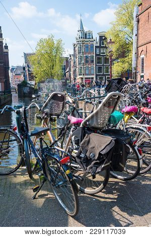 Amsterdam, Netherlands - April 20, 2017: Beautiful View Of Amsterdam Canals With Bridge And Bikes. A