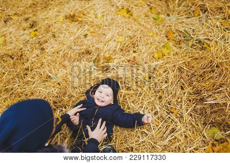 Little Cute Child Baby Boy Walk In Fall Park, Sit, Lay In Pile Of Straw, Have Fun In Dry Yellow Autu