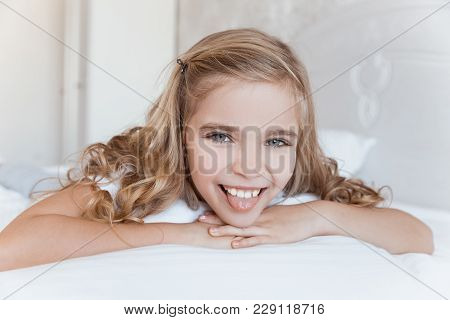 Smiling Kid Lying On Bed And Sticking Tongue Out