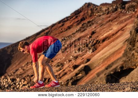 Runner athlete getting ready for training cardio exercise tying running shoes lace preparing for outdoor trail race in mountain landscape. Sports man working out exercising. Fitness active life.