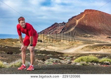 Tired runner on trail run feeling exhausted and dehydrated from the heat. Athlete man with smartwatch taking a break catching his breath looking at challenge ahead.