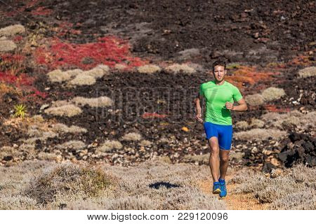 Sport athlete runner man running in mountain trail nature background. Focused motivated fit person training body jogging in rocky terrain summer outdoors.