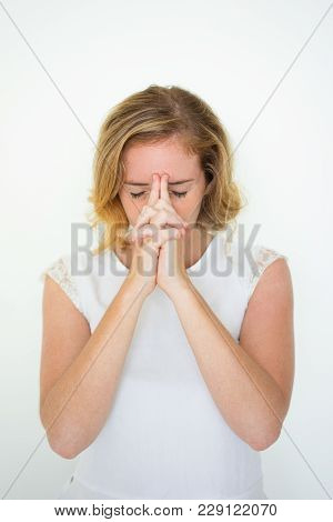 Closeup Portrait Of Young Pretty Woman Touching Forehead With Her Hands Clasped And Closed Eyes And