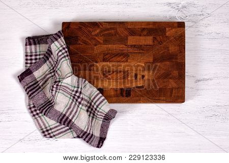 Old Wooden Cutting Board With Kitchen Towel On White Wooden Table. Top View, Copy Space. Cooking Bac