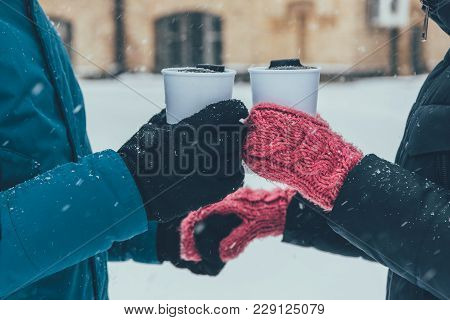 Partial View Of Couple With Hot Drinks Holding Hands On Street In Winter