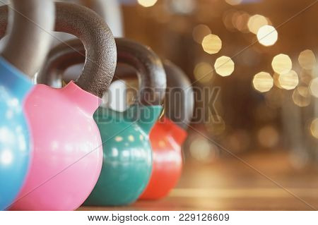 Colorful Kettlebells In A Row In A Gym. Colorful Kettlebells