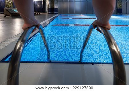 Man's Hand Holding A Handrail In A Swimming Pool