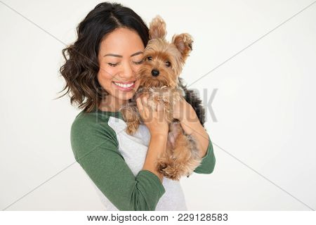 Closeup Portrait Of Smiling Young Attractive Woman Embracing Yorkshire Terrier With Her Eyes Closed.