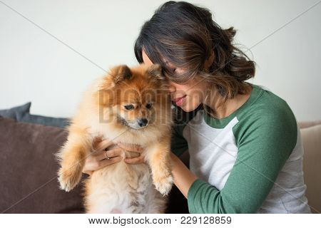 Closeup Portrait Of Serious Young Attractive Woman Embracing Pomeranian Spitz With Her Eyes Closed.