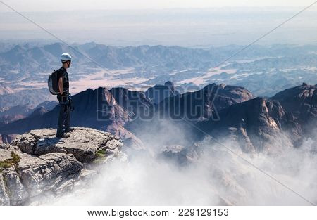 A mountain climber standing on a summit admires a beautiful, vast landscape view.