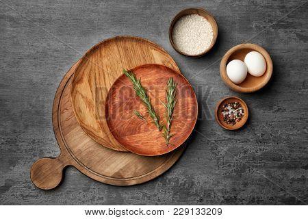 Wooden kitchen utensils with ingredients on grey background