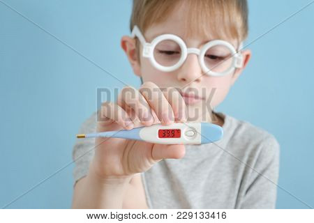 Little Boy With A Thermometer In His Hand. Increased Body Temperature. Face On Background