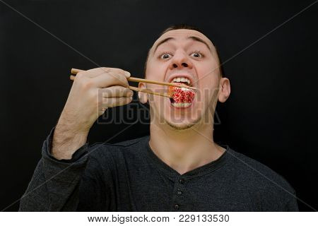 Hungry Man Eats Rolls With Chopsticks. Open Mouth. Black Background