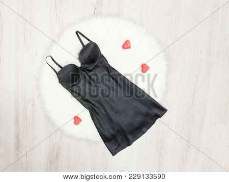 Fashion Concept. Black Satin Nightie On White Fur. Red Heartshaped Candles