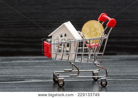 Shopping Cart With White House And Coin Bitcoin On A Black Background
