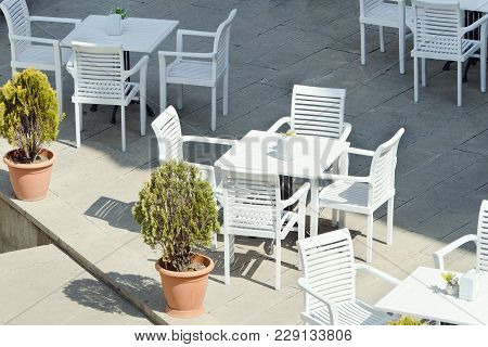 Empty White Tables Of A Street Cafe. Sunny Day