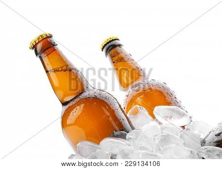 Bottles of beer in ice on white background