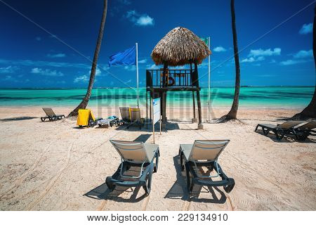 Palm Tree, Lounge Chairs And Lifeguard Station On The Tropical Island Beach Dominican Republic