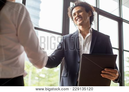 Happy Multiethnic Man Concluding Deal With Female Business Partner. Smiling Man Enjoying Collaborati