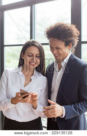 Happy Woman Showing Funny Photos On Phone To Coworker. Business Lady Showing New Application To Coll
