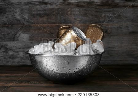 Bowl with cans of beer and ice on wooden background