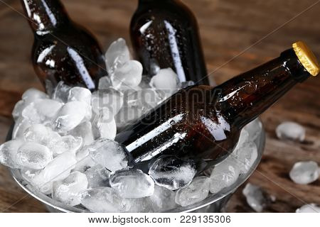 Bowl with bottles of beer in ice on wooden background, closeup