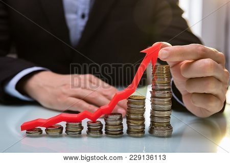 Businessperson Holding Arrow Over Increasing Stacked Coins