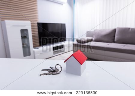 Close-up Of House Model And Key On White Desk In Living Room