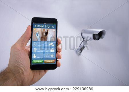 Human Hand Using Smart Home Application On Smartphone Near Cctv Camera Mounted On Wall